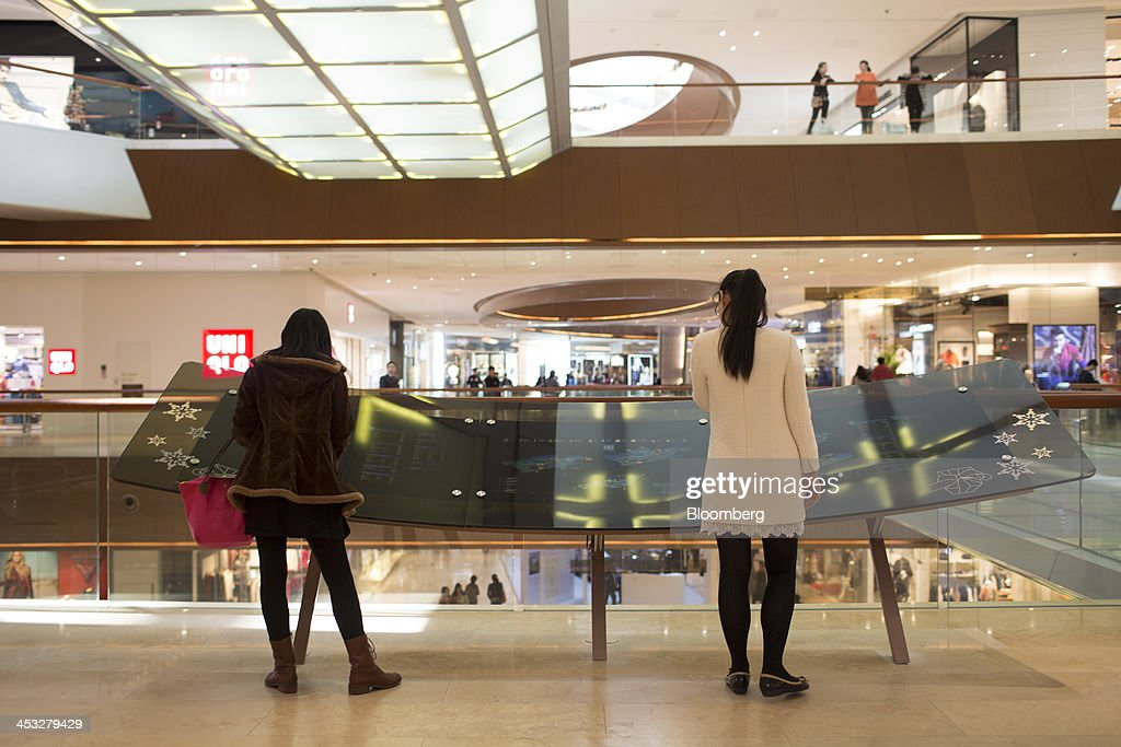 Shoppers look at a store directory inside the TaiKoo Hui shopping mall, operated by Swire Properties Ltd., in Guangzhou, China, on Saturday, Nov. 30, 2013. China's government may set its 2014 growth target at 7 percent, the Economic Information Daily reported on Dec. 3, citing the State Information Center. This compares with a goal of 7.5 percent for this year. Photographer: Brent Lewin/Bloomberg via Getty Images