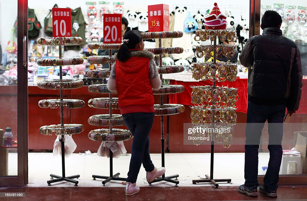 Shoppers look at accessories displayed at a store in the Wangfujing shopping district of Beijing, China, on Sunday, March 10, 2013. China's industrial output had the weakest start to a year since 2009 and lending and retail sales growth slowed, toughening challenges for a new leadership that wants to narrow the gap between rich and poor. Photographer: Tomohiro Ohsumi/Bloomberg via Getty Images