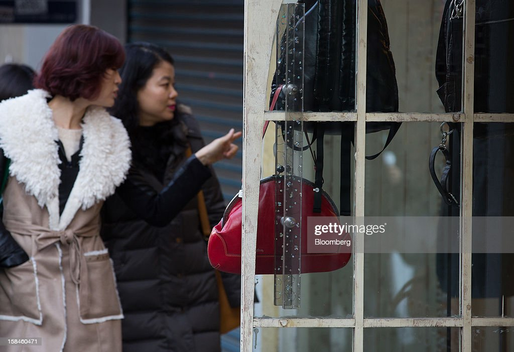 Shoppers look at bags displayed at a store on Garosugil street in the Gangnam district of Seoul, South Korea, on Saturday, Dec. 15, 2012. South Koreans vote on Dec. 19 to replace President Lee Myung Bak, whose five-year term ends in February. Photographer: SeongJoon Cho/Bloomberg via Getty Images