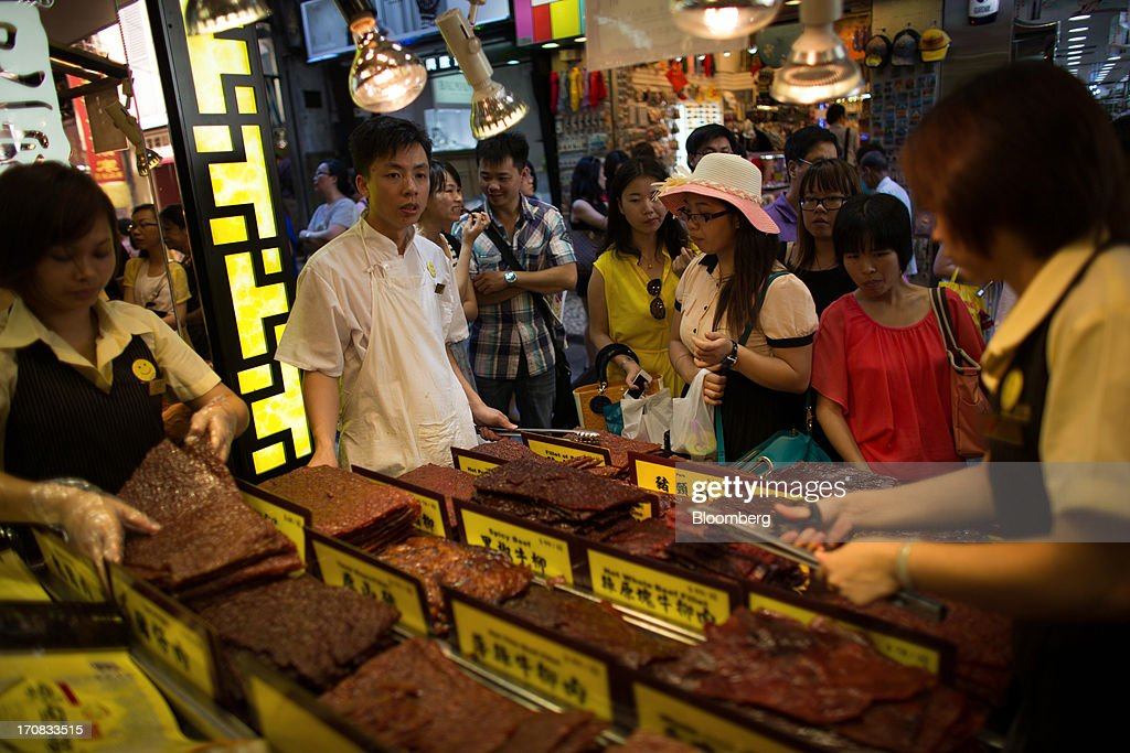Shoppers look at barbecued meats at a store in the city center of Macau, China, on Tuesday, June 18, 2013. Casino revenue in Macau, the only place in China where casino gambling is legal, rose 14 percent to a record of 304 billion patacas ($38 billion) in 2012. Photographer: Lam Yik Fei/Bloomberg via Getty Images