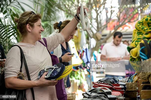 Shoppers look at flip flops at an Alpargatas SA Havaianas store in Sao Paulo Brazil on Saturday June 7 2014 Sao Paulobased Alpargatas SA the maker of...
