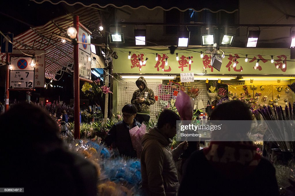 Shoppers look at flowers displayed for sale for the Lunar New Year at a flower market in the Mong Kok district of Hong Kong, China, on Sunday, Feb 7, 2016. The city's financial markets will close on Feb. 8 for the Lunar New Year holidays and resume trading on Feb. 11. Photographer: Billy H.C. Kwok/Bloomberg via Getty Images