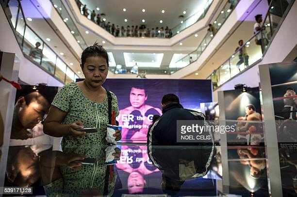 Shoppers look at memorabilia and photo exhibit featuring Muhammad Ali at the Ali Mall in Manila on June 10 2016 A bustling shopping mall forms an...