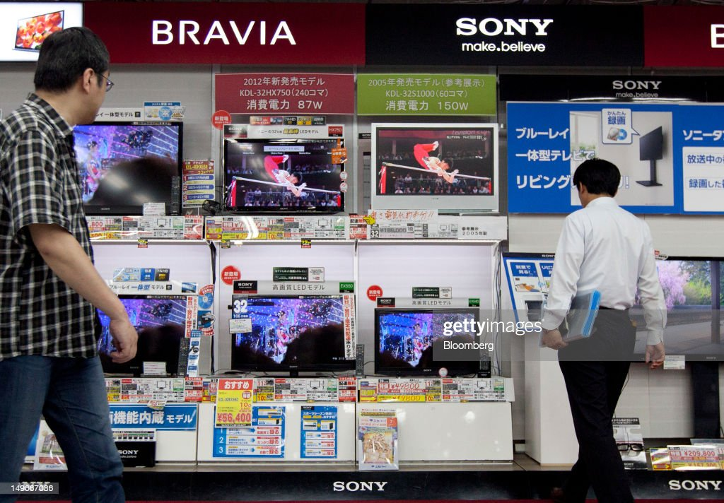 Shoppers look at Sony Corp. Bravia televisions at an electronics store in Tokyo, Japan, on Thursday, Aug. 2, 2012. Sony Corp., reeling from four consecutive annual losses, cut its full-year profit forecast as Japan's biggest exporter of consumer electronics suffers from slowing demand while the yen's gain erodes overseas earnings. Photographer: Tomohiro Ohsumi/Bloomberg via Getty Images
