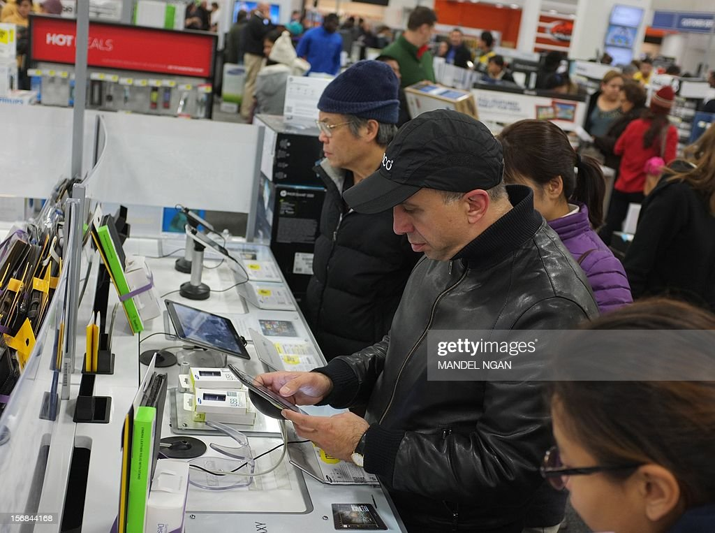 Shoppers look at tablet computers inside of a Best Buy store during their Black Friday sale which started at midnight on November 23, 2012 in Rockville, Maryland. Thanksgiving, the last US holiday undisturbed by mass commercialization, is now victim to the ever advancing Christmas shopping season, with stores welcoming shopaholics before the family turkey can be taken from the oven.