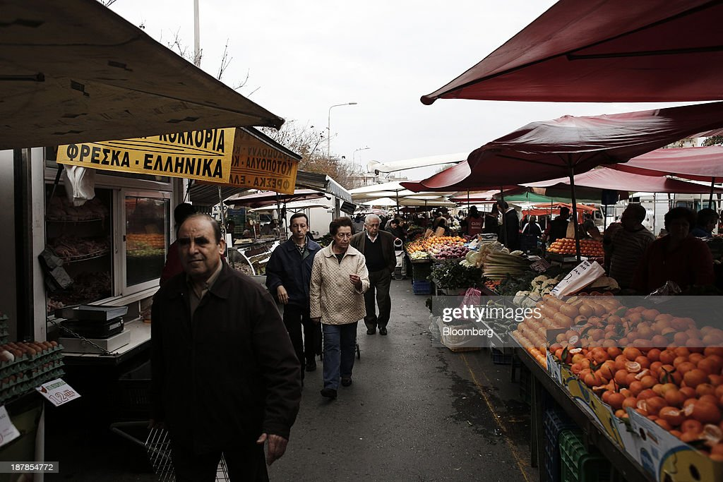 Shoppers look for fresh fruit and vegetables for sale at a farmer's market in the Toumpa district of Thessaloniki, Greece, on Wednesday, Nov. 13, 2013. Greece 'is following a fiscal adjustment program that aims to make the country's public finances sustainable on a permanent basis,' Finance Minister Yannis Stournaras told lawmakers during the debate, after holding talks with the troika earlier in the week. Photographer: Konstantinos Tsakalidis/Bloomberg via Getty Images