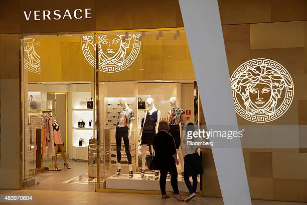 Shoppers look in the window of the Gianni Versace SpA store at the Village Mall in Rio de Janeiro Brazil on Wednesday Aug 12 2015 Cartier and Louis...
