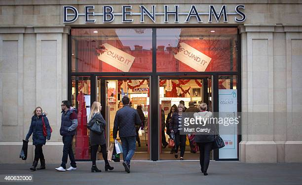 Shoppers looking for Christmas gifts enter Debenhams on December 18 2014 in Bath England With less than a week until Christmas traditional high...