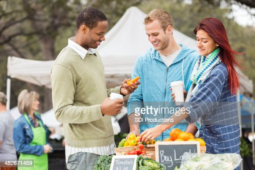 Shoppers looking through vegetables at the local farmers market