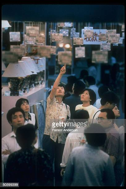 Shoppers looking up at overhead price cards in lamp section at Beijing Department Store re inflationary economy bringing numerous price rises