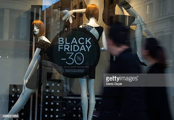 Shoppers looks at advertising for 'Black Friday' discounts at a retail store on November 27 2015 in Madrid Spain Originating in the USA as a sales...