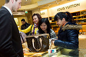 Shoppers make a purchase using a UnionPay debit card at Harrods on February 3 2011 in London England UnionPay is the sole debit card provider in...