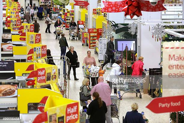 Shoppers make their way along the central aisle at the Tesco Basildon Pitsea Extra supermarket operated by Tesco Plc in Basildon UK on Tuesday Dec 1...