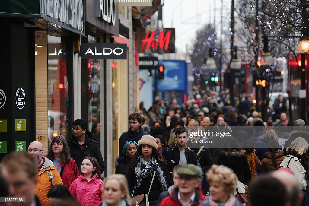 Shoppers make their way down Oxford Street on December 24 2012 in London England Many high street retailers have started their sales two days early...