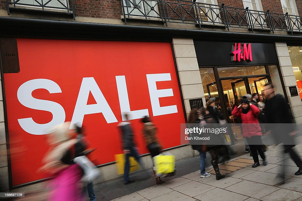 Shoppers make their way past a sale sign outside a clothing store on Oxford Street on December 24, 2012 in London, England. Many high street retailers have started their sales two days early this year on what is expected to be the busiest shooping day of the year.