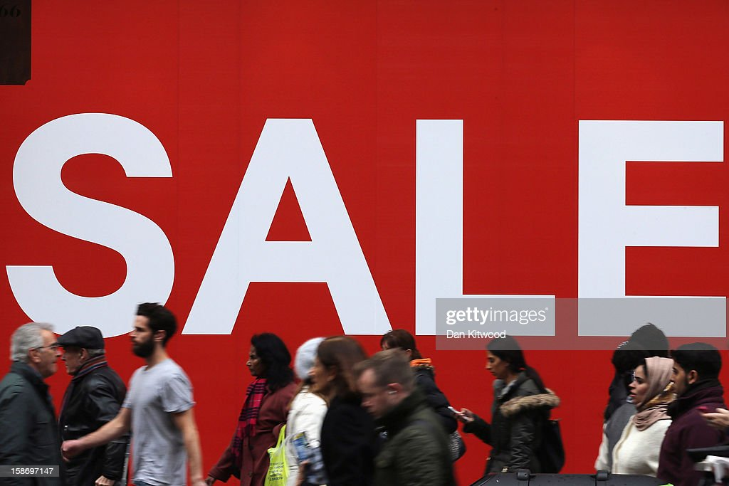 Shoppers make their way past a sale sign outside a clothing store on Oxford Street on December 24 2012 in London England Many high street retailers...