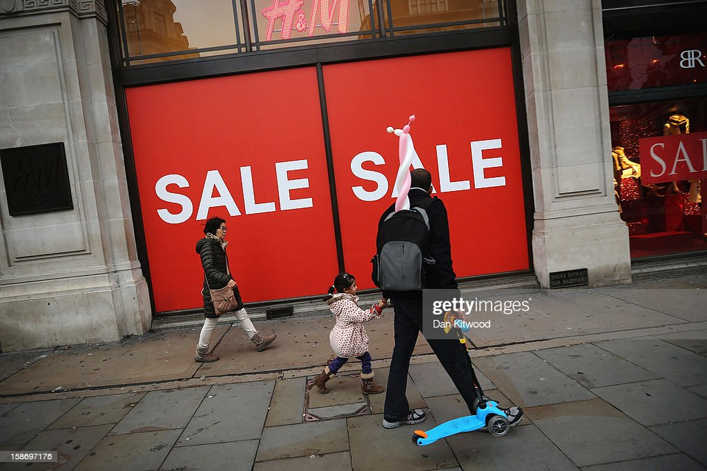 Shoppers make their way past a sale sign outside a clothing store on Regent Street on December 24, 2012 in London, England. Many high street retailers have started their sales two days early this year on what is expected to be the busiest shooping day of the year.
