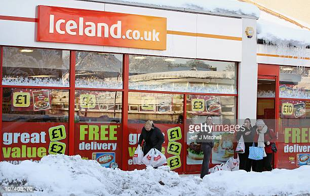 Shoppers make their way through the snow on December 8 2010 in Whitburn Scotland Work continues to keep the main road networks clear in Scotland...