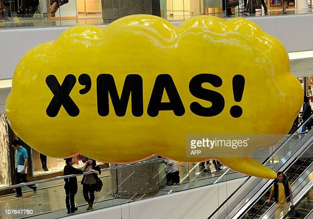 Shoppers move around a mall decorated with huge plastic speech bubbles for Christmas in Hong Kong on December 14 2010 Christmas shoppers were out in...