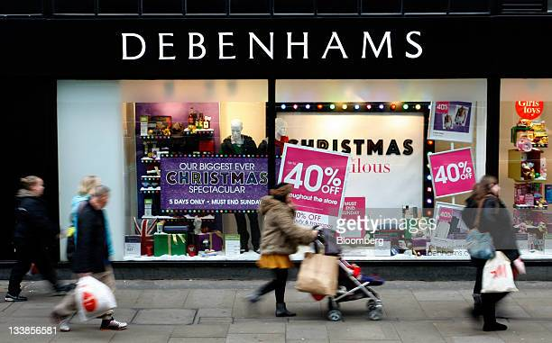 Shoppers pass a Christmas window display at a Debenhams store in Manchester UK on Sunday Nov 20 2011 UK retail sales unexpectedly rose in October as...