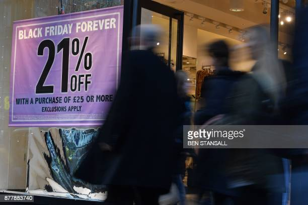 Shoppers pass a promotional sign for 'Black Friday' sales discounts on Oxford Street in London on November 23 2017 Black Friday is a sales offer...
