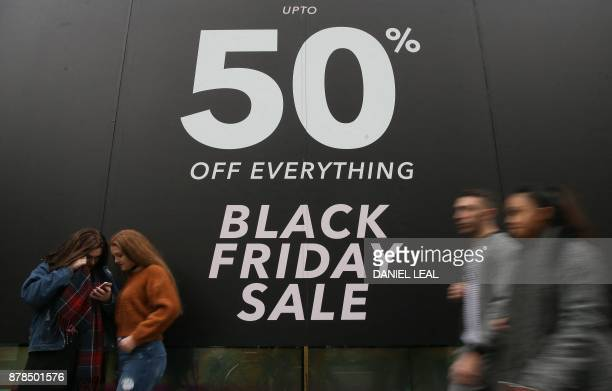 Shoppers pass a promotional sign for 'Black Friday' sales discounts on Oxford Street in London on November 24 2017 Black Friday is a sales offer...