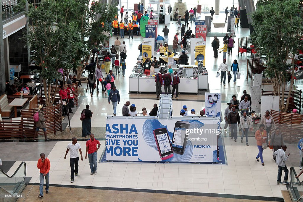 Shoppers pass a promotional stand for Nokia Asha smartphones during an 'activation day' event by Nokia Oyj in Maponya Mall in Soweto, South Africa, on Saturday, March 16, 2013. Nokia, based in Espoo, Finland, introduced three phones for its Asha line, sold primarily in emerging markets. Photographer: Nadine Hutton/Bloomberg via Getty Images