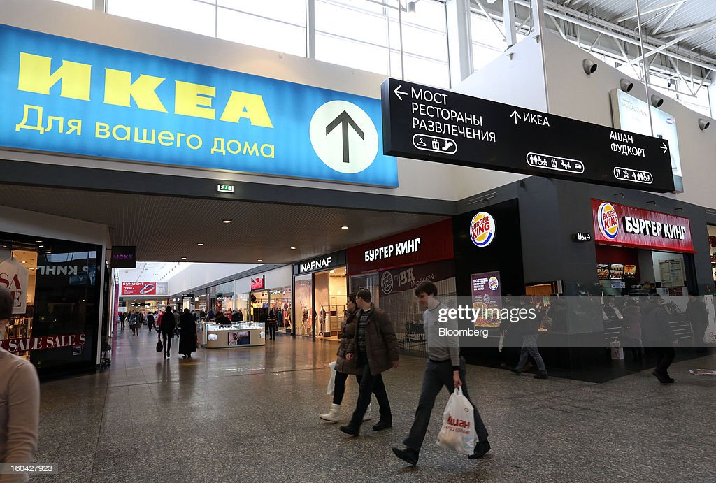 Shoppers pass a sign indicating the direction to an Ikea Group store above retail outlets at the MEGA Belaya Dacha shopping complex, constructed by the real estate development arm of Inter Ikea Systems BV and one of Europe's largest malls, in Moscow, Russia, on Thursday, Jan. 31, 2013. Russian shopping-mall construction may climb to a record this year as retailers take advantage of rising sales by moving into bigger, more modern buildings, Cushman & Wakefield Inc. said. Photographer: Andrey Rudakov/Bloomberg via Getty Images