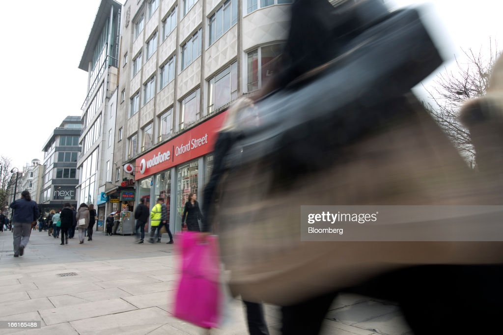 Shoppers pass a Vodafone Group Plc store on Oxford Street in London, U.K., on Monday, April 8, 2013. Vodafone Group Plc is restating its results going back two fiscal years as new international accounting rules for joint ventures cut historical revenue and earnings. Photographer: Simon Dawson/Bloomberg via Getty Images