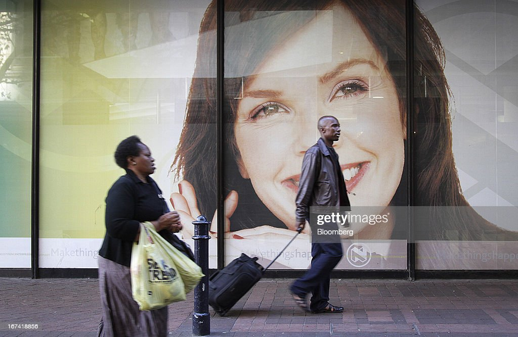 Shoppers pass an advertising billboard for Nedbank Ltd. on a street in Cape Town, South Africa, on Wednesday, April 24, 2013. South Africa's gross domestic product is forecast to expand 2.6 percent this year, compared with 2.5 percent in 2012, according to the country's central bank. Photographer: Nadine Hutton/Bloomberg via Getty Images