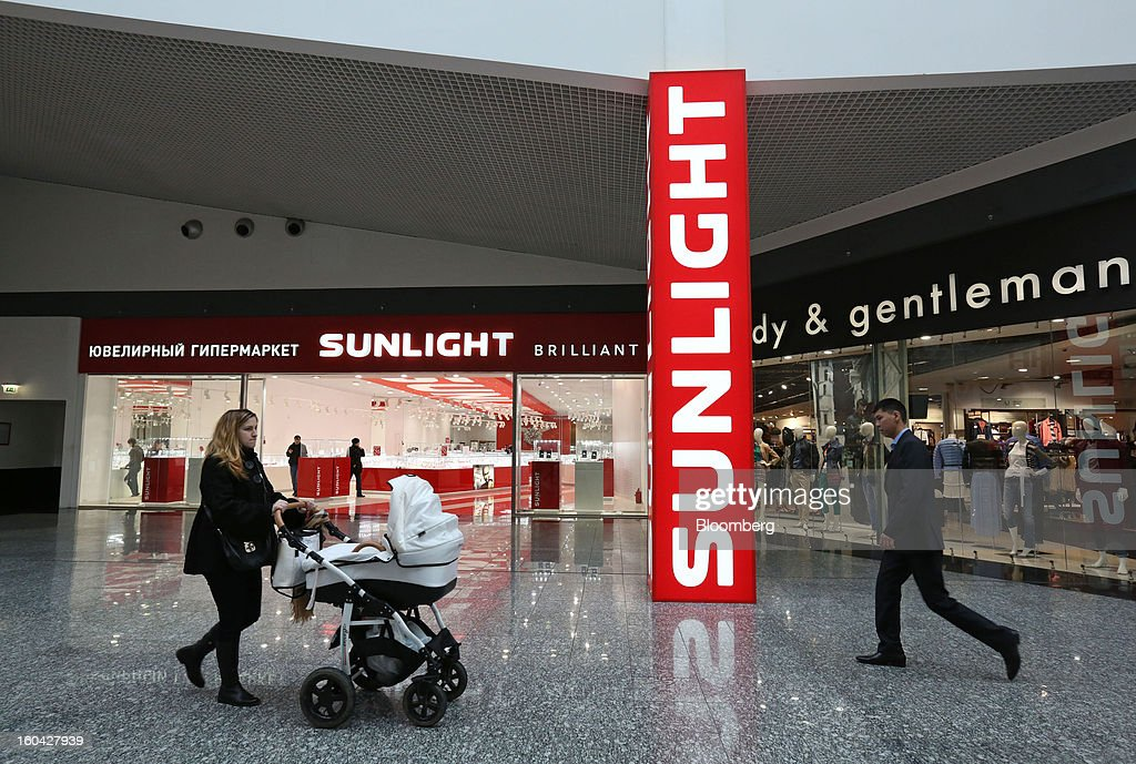 Shoppers pass an illuminated sign outside a Sunlight supermarket at the MEGA Belaya Dacha shopping complex, constructed by the real estate development arm of Inter Ikea Systems BV and one of Europe's largest malls, in Moscow, Russia, on Thursday, Jan. 31, 2013. Russian shopping-mall construction may climb to a record this year as retailers take advantage of rising sales by moving into bigger, more modern buildings, Cushman & Wakefield Inc. said. Photographer: Andrey Rudakov/Bloomberg via Getty Images