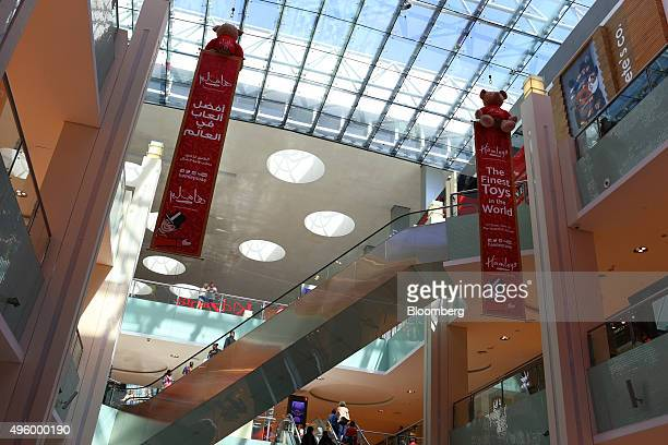 Shoppers pass between floors on escalators beneath advertisements for Hamleys Plc toy store inside the Dubai Mall retail complex operated by Emaar...