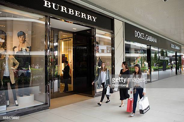 Shoppers pass Burberry Group Plc left and Dolce Gabbana Srl luxury fashion stores in the Zorlu shopping mall in Istanbul Turkey on Sunday Aug 10 2014...