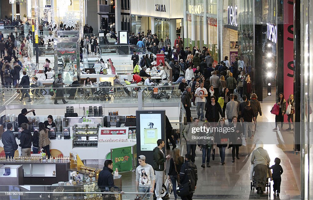 Shoppers pass clothing stores and food outlets as they walk through the Westfield Stratford City shopping mall in London, U.K., on Thursday, Dec. 27, 2012. Overall Christmas shopping in the U.K. was similar to last year, according to the British Retail Consortium. Photographer: Chris Ratcliffe/Bloomberg via Getty Images