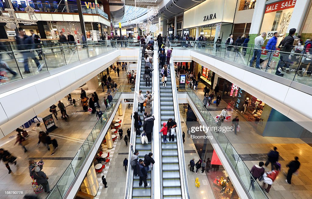 Shoppers pass clothing stores and outlets inside the Westfield Stratford City shopping mall in London, U.K., on Thursday, Dec. 27, 2012. Overall Christmas shopping in the U.K. was similar to last year, according to the British Retail Consortium. Photographer: Chris Ratcliffe/Bloomberg via Getty Images