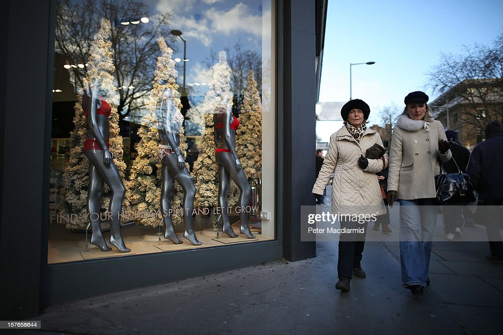 Shoppers pass festive shop window displays on King's Road in Chelsea on December 5, 2012 in London, England. The Chancellor of the Exchequer George Osborne has stated that the United Kingdom's economy is still struggling during his Autumn budget statement to Parliament.