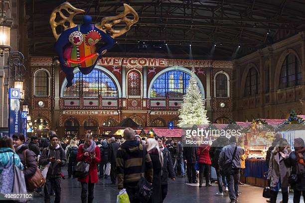 Shoppers pass festively decorated stalls as a Christmas tree stands illuminated at a Christmas market in the main railway station in Zurich...
