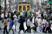 Shoppers pass in front of a cable car as they walk through the Union Square shopping district December 24 2004 in San Francisco California Retailers...