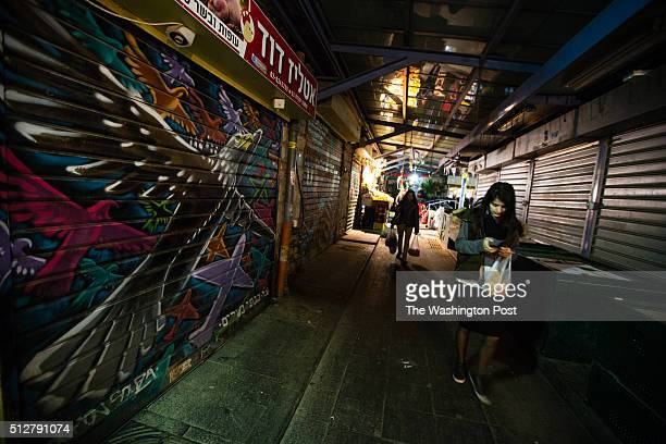 Shoppers pass in front of a graffiti depicting fanciful animals which was painted over a closed shutter at the Mahane Yehuda Market often called 'The...