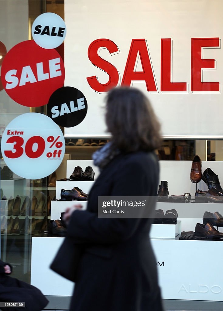 Shoppers pass sale signs in shop windows on December 10, 2012 in Bristol, England. With internet shopping still on the rise, many traditional retailers claim this Christmas could be the one that will determine the future of the high street.