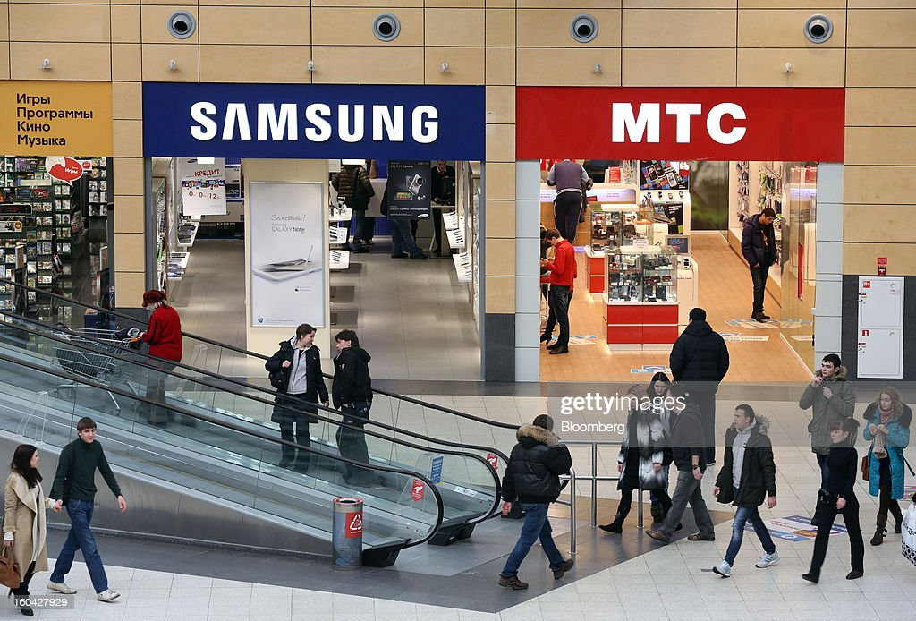 Shoppers pass Samsung Electronics Co. and MTC-branded stores at the MEGA Belaya Dacha shopping complex, constructed by the real estate development arm of Inter Ikea Systems BV and one of Europe's largest malls, in Moscow, Russia, on Thursday, Jan. 31, 2013. Russian shopping-mall construction may climb to a record this year as retailers take advantage of rising sales by moving into bigger, more modern buildings, Cushman & Wakefield Inc. said. Photographer: Andrey Rudakov/Bloomberg via Getty Images