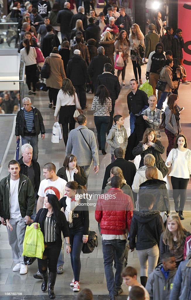 Shoppers pass stores as they walk through the Westfield Stratford City shopping mall in London, U.K., on Thursday, Dec. 27, 2012. Overall Christmas shopping in the U.K. was similar to last year, according to the British Retail Consortium. Photographer: Chris Ratcliffe/Bloomberg via Getty Images