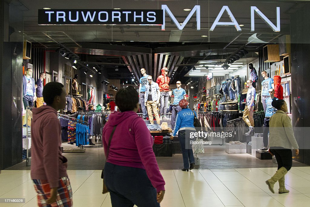 Shoppers pass the entrance to a Truworths International Ltd. Man retail store in the Sandton district of Johannesburg, South Africa, on Thursday, Aug. 22, 2013. Massmart Holdings Ltd., the South African food and goods wholesaler owned by Wal-Mart Stores Inc., said revenue growth continued to slow in August after a downturn in consumer spending hurt first-half earnings. Photographer: Nadine Hutton/Bloomberg via Getty Images