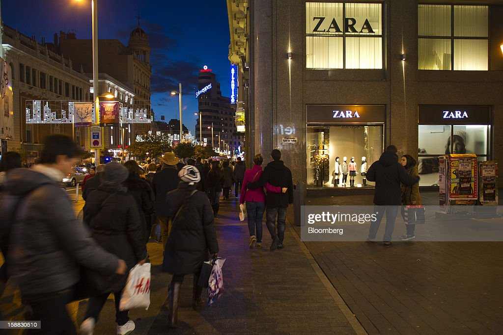 Shoppers pass the illuminated window displays of a Zara fashion store, operated by Inditex SA, in central Madrid, Spain, on Saturday, Dec. 29, 2012. Spain's economic activity kept falling in the fourth quarter, Bank of Spain says. Photographer: Angel Navarrete/Bloomberg via Getty Images