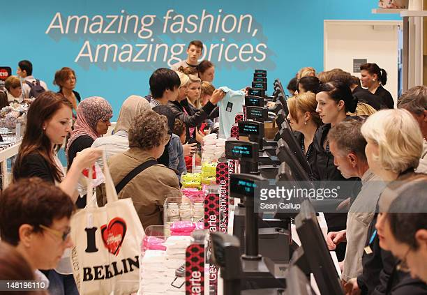 Shoppers pay for clothes at the cash registers at a Primark clothing store a day after the store's opening on July 12 2012 in Berlin Germany Primark...