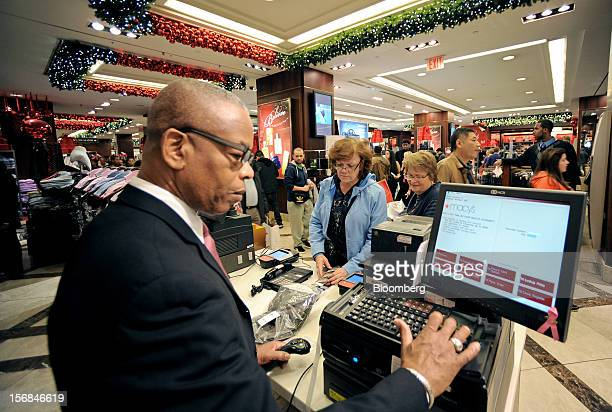 Shoppers pay for items at a Macy's Inc store in New York US on Friday Nov 23 2012 Discount store shoppers are prepared to wait in long lines on Black...