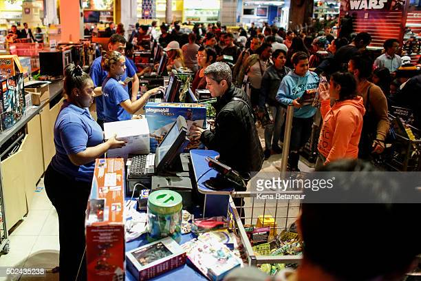 Shoppers pay for items at a Toys'R'Us store on December 24 2015 in New York City Lastminute shoppers get some of the best deals many of the major...