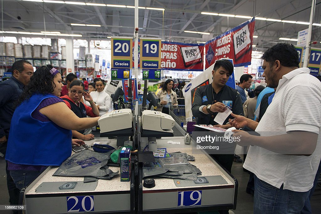 Shoppers pay for their merchandise inside a Sam's Club store in Mexico City, Mexico on Saturday, Nov. 17, 2012. El Buen Fin, Mexico's equivalent of Black Friday, when the year's biggest discounts are offered by participating stores, is held on the third weekend of November and will run through Nov. 19. Photographer: Susana Gonzalez/Bloomberg via Getty Images