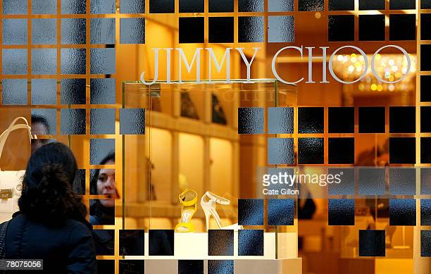 A shoppers peers in the window of the store Jimmy Choo on Bond Street on November 23 2007 in London London's stores have had their windows decorated...