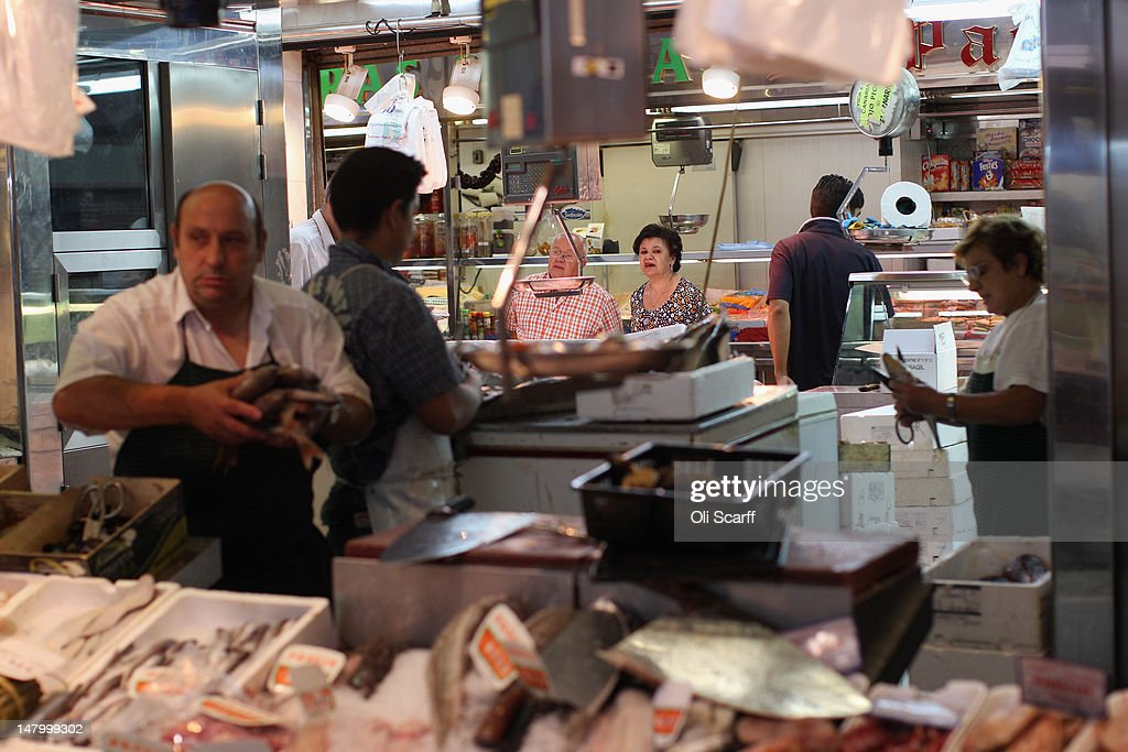 Shoppers peruse the stalls in an indoor market near the Plaza de Cascorro on July 7, 2012 in Madrid, Spain. Despite having the fourth largest economy in the Eurozone, the economic situation in Spain remains troubled with their unemployment rate the highest of any Eurozone country. Spain is currently administering billions of euros of spending cuts and tax increases in a bid to manage its national debt. Spain also has access to loans of up to 100 billion euros from the European Financial Stability Facility which will be used to rescue the country's banks that have been badly affected by a crash in property prices.